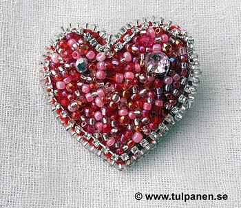 Hjärtformad brosch med röda och silvriga pärlor.