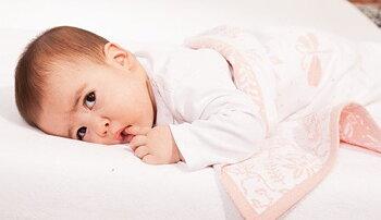 Babyfilt med äng och namn. Rosa