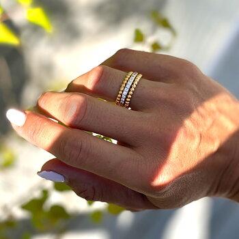 Tunn semi alliansring i guld på stål med zirconia stenar. Text: älskad