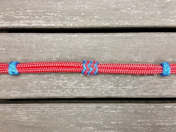 Neck rope with knot adjustment and decorative knots