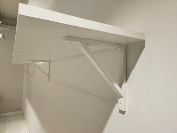 White painted wall shelves with brackets