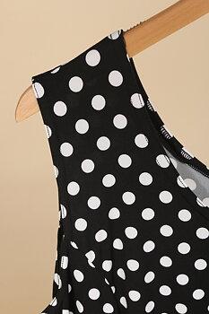 Klänning i ärmlös vippig modell, svartvit prickig